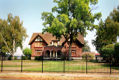 Older Historic Brick Home. Frontal view of a large old substantial brick country home in a spacious landscaped setting, with wrought iron fencing in front Royalty Free Stock Images