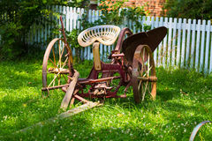 Older Horse Drawn Plow in Yard. Lancaster, PA – July 13, 2016: An old, horse-drawn plow, in a yard near a white picket fence on the grounds of the Landis Stock Photos
