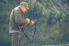Older hunter cocks the gun Royalty Free Stock Photo
