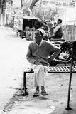 Older India Man Sits on Bench. A high contrast black and white image of an Indian man sitting crosslegged on a bench at a chai stand on the side of the road Stock Photo