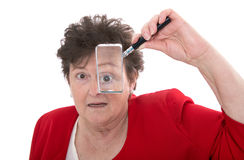 Older isolated woman holding magnifying glass and is shocked. Royalty Free Stock Image