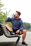 Older jogger sitting on bench with water bottle Royalty Free Stock Image