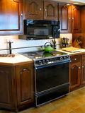 Older kitchen and stove. Cherry cabinets Stock Image