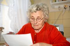 Older lady. An older lady sits on a chair and read a letter Royalty Free Stock Photography