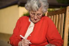 Older lady. An older lady sits on a chair and notes something or solves a mystery Royalty Free Stock Photo