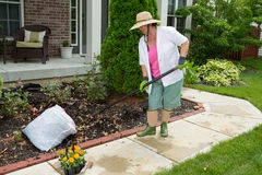 Older lady doing cleaning work in the yard Royalty Free Stock Image