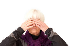 Older lady with hands over her eyes. On white stock photography