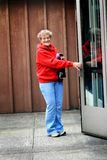 Older lady opening door Royalty Free Stock Photo