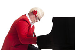 Older lady in red playing the grand piano. Elderly lady in red playing the grand piano in studio with white background royalty free stock images