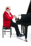 Older lady in red playing the grand piano. Elderly lady in red playing the grand piano in studio with white background royalty free stock photos