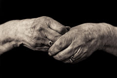 Older lady`s hands. Widows grief in old age concept. Black and white image of an older lady`s hands clasped in grief wearing her late husbands wedding ring Royalty Free Stock Images