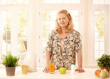 Older lady standing in kitchen Stock Images