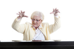 Older lady in yellow playing the piano. Elderly lady in yellow playing the piano in studio with white background royalty free stock photos