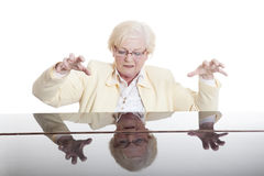 Older lady in yellow playing the piano. Elderly lady in yeloow playing the grand piano in studio with white background royalty free stock image