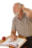 Older learner. Older man trying to think while reading a textbook back in school Stock Photo