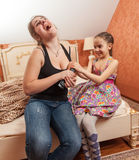 Older and little sister having fight for TV remote Stock Photos