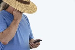 Older long gray haired man in wide brim straw hat and tee shirt shade his eyes to see cell phone - isolated on white.  stock images