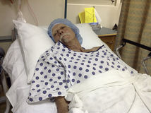 Older male hospital patient awaiting surgery. Senior male lies in hospital bed, wearing gown and blue cap, sleeping before a medical procedure or surgery Stock Images