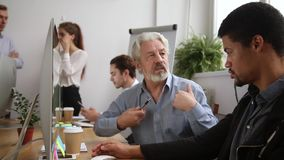 Older male mentor helping teaching new employee training intern. Older male mentor helping teaching new employee explaining intern giving instructions in office stock footage