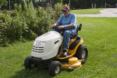 Older Male Mowing Grass With His Riding Mower Stock Photography