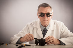 Camera Repair. An older male wearing a white lab coat and repairing electronic equipments, like a technician or a repair man Stock Image