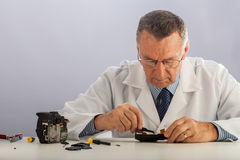 Camera Technician. An older male wearing a white lab coat and repairing electronic equipments, like a technician or a repair man Royalty Free Stock Photos