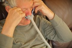 Senior man on sofa adjusts a CPAP device stock image