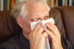 Seated senior man blowing his nose royalty free stock images