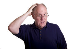 An Older Man in Blue Shirt Rubbing Bald Head Stock Photo