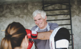 Older man boxing in gym. Older men boxing in gym. Senior men with personal trainer Royalty Free Stock Photography