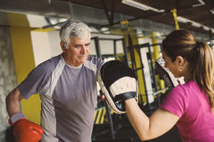 Older man boxing in gym. Older men boxing in gym. Senior men with personal trainer Stock Images