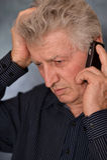 Older man calling. Portrait of a sad older man calling on a gray background Stock Image