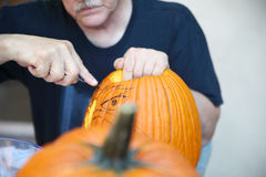 Older man carves a Halloween pumpkin outdoors. Guided by his sketch, an older man carves a jack o' lantern Stock Images