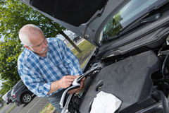 Older man checking levels and servicing car. Older man checking levels and servicing his car Royalty Free Stock Photos