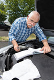 Older man checking levels and servicing car Royalty Free Stock Photography