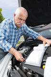 Older man checking levels and servicing car. Older man checking levels and servicing his car Royalty Free Stock Image