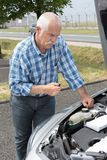 Older man checking levels and servicing car. Older man checking levels and servicing his car Stock Photography