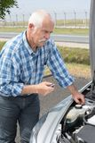 Older man checking levels and servicing car Stock Photo