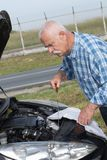 Older man checking levels and servicing car. Older man checking levels and servicing his car Royalty Free Stock Photo
