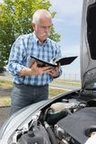 Older man checking levels and servicing car Royalty Free Stock Images