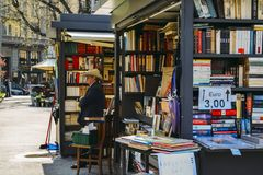 An older man with a cowboy hat sells books on the street. Milan, Italy - April 14, 2018: An older man with a cowboy hat sells books on the street Stock Photos