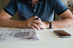 Older man with crossword and phone. Older man in blue shirt leaning on table holding pen with crossword and phone in front of him (cropped and selective focus royalty free stock photo