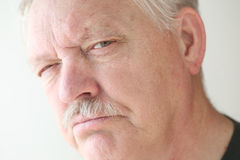 Older man with disbelieving expression. Senior man with a suspicious or skeptical expression Royalty Free Stock Photography