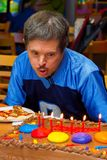 Down Syndrome Man Blows Out Birthday Candles. An older man with Down Syndrome blows out candles on his birthday cake at a pizza party in his honor. He looks very royalty free stock image