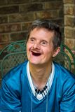 Older Man With Downs Syndrome and No Teeth Delightful Smile. An older man with Downs Syndrome gives a huge smile. The delight on his face shows off the fact that royalty free stock photos
