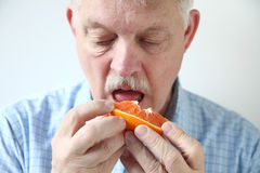 Older man eating orange Stock Photography