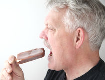 Senior man with ice cream bar profile view Stock Image