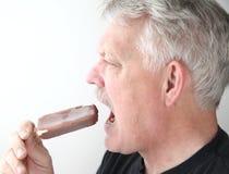 Senior man with ice cream bar profile view Stock Image