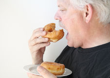 Older man eats glazed doughnut Royalty Free Stock Images
