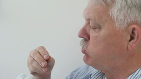 Older man eats potato chips stock footage